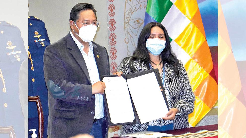 El presidente Luis Arce junto a la representante del Movimiento para la Devolución de Aportes Rosalin Machaca en la promulgación de la ley. APG