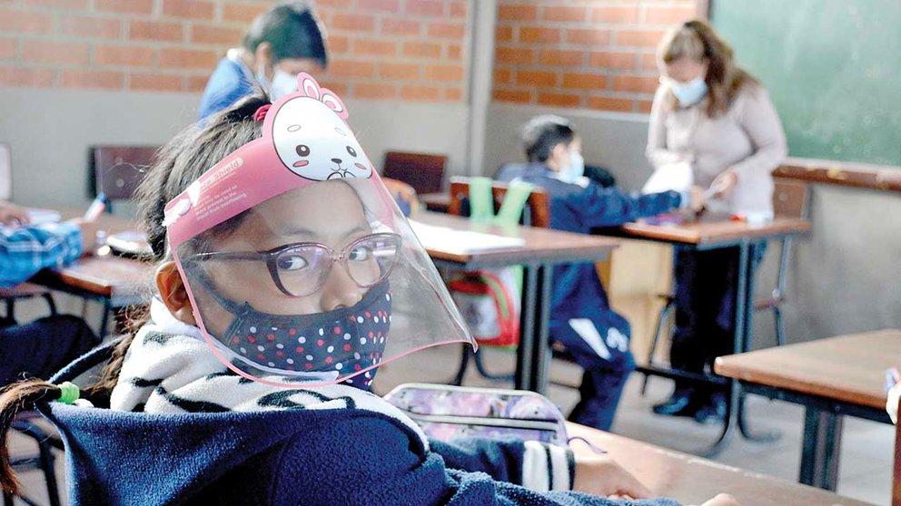 Una niña con visor y barbijo pasa clases en un establecimiento educativo. DICO SOLÍS