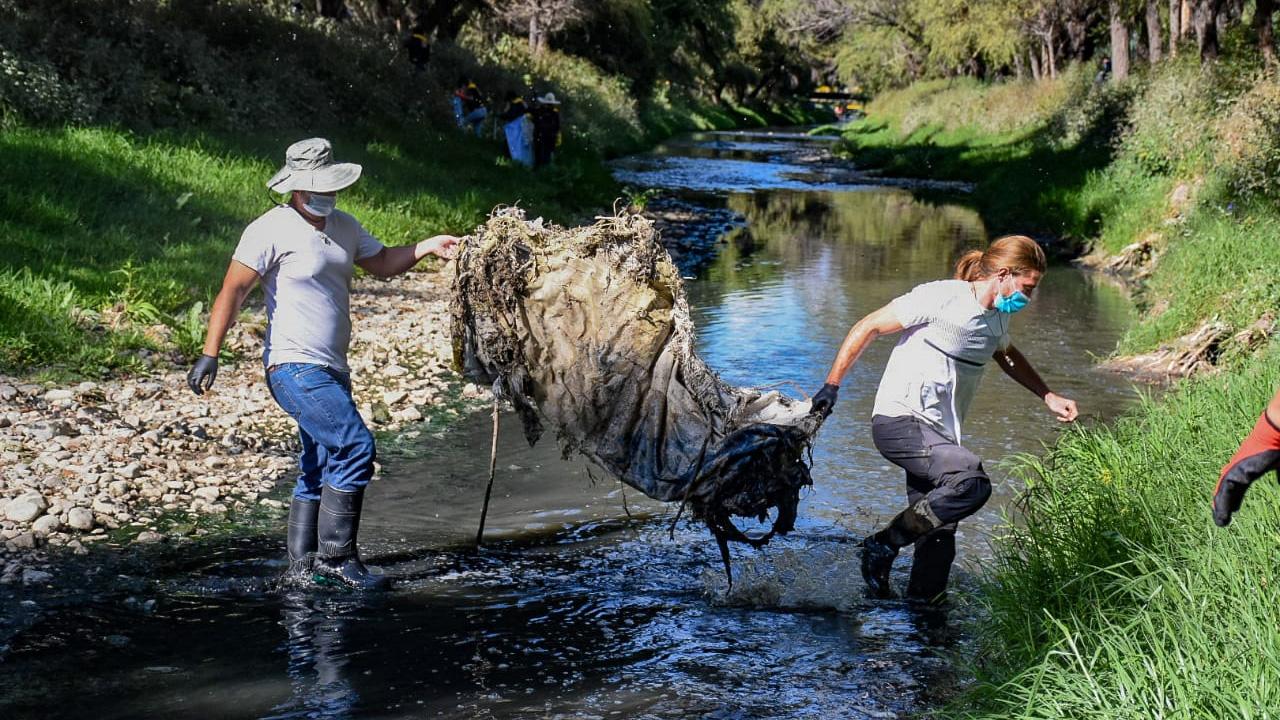 El concejal electo Manfred Reyes Villa Jr. y el turista francés Alexis Dessard en plena tarea de limpieza del río Rocha. DICO SOLÍS